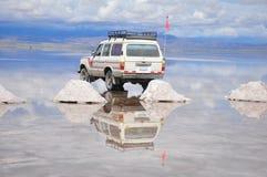 Reflexión del jeep en Salar inundado de Uyuni Fotos de archivo libres de regalías