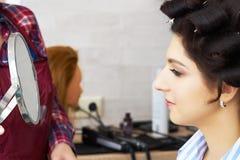 Reflexión del peinado del cliente femenino en espejo Concepto de moda y de belleza Morenita hermosa con el borrachín foto de archivo libre de regalías