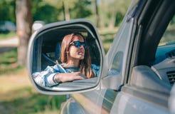 Reflexión en el espejo de la vista lateral de la conducción de la mujer Imágenes de archivo libres de regalías