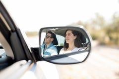 Reflexión en el espejo de la vista lateral de los pares que viajan en coche Imagen de archivo