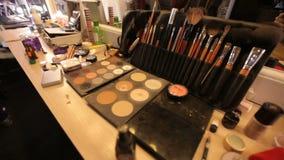 Reflexión en el espejo de un modelo de la muchacha en un estudio del arte Artista de maquillaje profesional de los cosméticos en  almacen de video