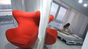 Reflexión en el modelo joven del espejo que presenta en cama en estudio de la foto almacen de video