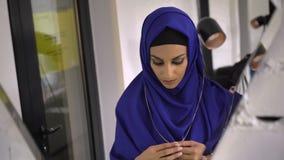 Reflexión en espejo de la mujer musulmán joven en el hijab que intenta en el collar y la pulsera en joyería metrajes