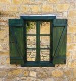Reflexión en una ventana con los obturadores de madera verdes Foto de archivo libre de regalías