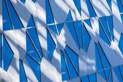Reflexión entonada azul del cielo en la ventana del edificio con el sol y el le Imagen de archivo