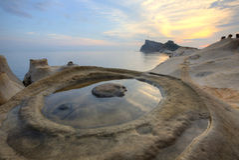 Reflexión hermosa del cielo atractivo de la salida del sol en el parque geológico de la costa de Yehliu con formaciones de roca d fotografía de archivo