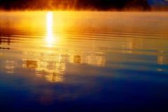 Reflexión hermosa del sol en abajo en niebla de oro de la mañana Foto de archivo