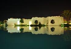 Reflexión oriental de la noche de los edificios del estilo en piscina fotografía de archivo