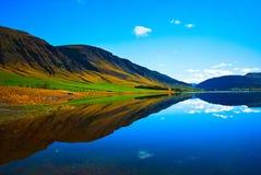 Reflexión perfecta de la montaña en el lago inmóvil Imagen de archivo
