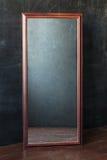 Reflexión rectangular clásica del withot del espejo que se coloca en el cuarto vacío con la pared negra Foto de archivo