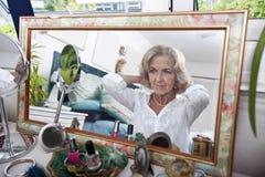 Reflexión de espejo de la mujer mayor que pone en el collar en casa Fotografía de archivo