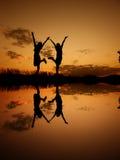 Reflexión de las mujeres Relax que se colocan y de la silueta de la puesta del sol Foto de archivo