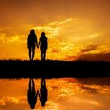 Reflexión de las mujeres Relax que se colocan y de la silueta de la puesta del sol Fotos de archivo libres de regalías