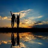 Reflexión de las mujeres Relax que se colocan y de la silueta de la puesta del sol Fotografía de archivo libre de regalías
