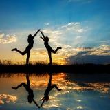 Reflexión Relax de dos mujeres que se colocan y de la silueta de la puesta del sol Foto de archivo libre de regalías