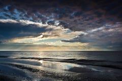Reflexion auf dem Sand über dynamischem Himmel Stockfotografie