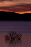 Reflexion auf glattem See am Sonnenuntergang, drastischer Himmel Lizenzfreies Stockbild