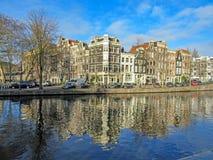 Reflexion av Amsterdam i stadskanal arkivfoton