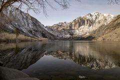 Reflexion av berg på en glas- iskall sjö i vinter royaltyfri fotografi