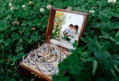 Reflexion av bruden och brudgummen i spegeln av träasken med guldbröllopcirkeln fotografering för bildbyråer
