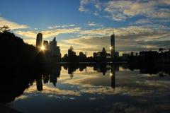 Reflexion av byggnader av staden på soluppgång Arkivbild