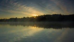 Reflexion av de första strålarna av gryningsolljus i sjön Royaltyfri Bild
