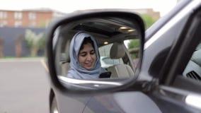 Reflexion av den härliga unga kvinnan i hijabrengöringsduk som surfar i hennes bil stock video