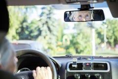 Reflexion av den höga kvinnan i spegel för bakre sikt Arkivfoto