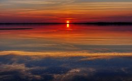 Reflexion av den molniga himlen på solnedgången Arkivfoto