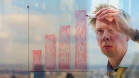 Reflexion av en affärsman som drar en graf på ett fönster arkivfilmer