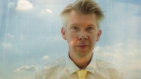 Reflexion av en dagdrömma affärsman som ser ut ur ett fönster lager videofilmer