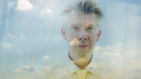 Reflexion av en dagdrömma affärsman som ser ut ur ett fönster arkivfilmer