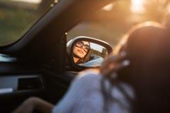 Reflexion av en härlig ung mörker-haired flicka i solglasögon i en sidospegel av en bil arkivbild
