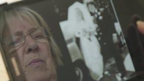 Reflexion av en hög kvinna som ser gamla foto på en minnestavladator lager videofilmer