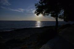 Reflexion av en inställningssol på havsyttersida royaltyfri foto