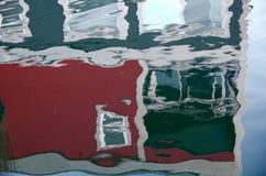 Reflexion av en röd och grå sjöbod Arkivfoto