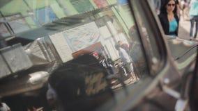 Reflexion av folk i fönster av den gamla bilen spegel swallowtail för sommar för fjärilsdaggräs solig händelse Cyklistmöte stock video