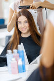 Reflexion av frisören som gör hårstil för kvinna arkivbilder