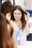 Reflexion av frisyren av klienten i spegel royaltyfria bilder