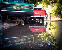 Reflexion av gamla bilar i en pöl royaltyfri foto