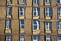 Reflexion av gammal byggnad ut ur exponeringsglas av en modern corpaoratebyggnad (de mest förvridna fönstren kan verka lite unshar Arkivfoton