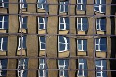 Reflexion av gammal byggnad ut ur exponeringsglas av en modern corpaoratebyggnad (de mest förvridna fönstren kan verka lite unshar Arkivfoto