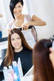 Reflexion av hårstylisten som gör frisyr för kvinna arkivbild