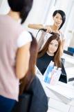 Reflexion av hårstylisten som gör frisyren för kvinna royaltyfri fotografi