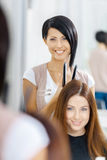Reflexion av hårstylisten som gör hårstil för kvinna Arkivbilder
