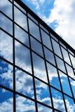 Reflexion av himlen och molnen i fönstren av byggnad Arkivfoto