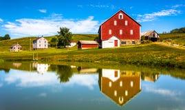 Reflexion av huset och ladugården i ett litet damm, i lantliga York Coun Arkivfoto