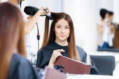 Reflexion av kosmetologen som gör frisyren för kvinna royaltyfri foto