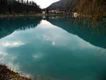 Reflexion av kullar, berg, byn och himmel i turquisevatten royaltyfri fotografi