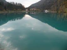 Reflexion av kullar, berg, byn och himmel i turquisevatten royaltyfria bilder